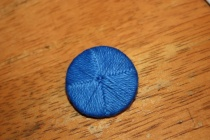 A Death Head button; blue cotton thread wrapped around a disc.
