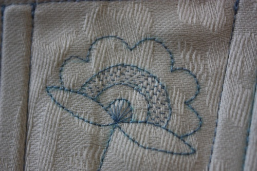 The detail of the central embroidered flower.