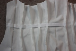 The waist tape is being attached to each seam allowance so that no stitching is seen on the outside.