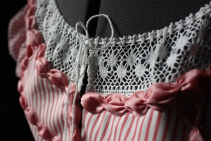 The front of the bodice, showing the cord lacing up the insertion lace at the front.