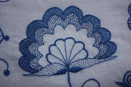 The centre flower; stitched with backstitch, seed stitch, satin stitch, chain stitch, french knots, and fly stitch.