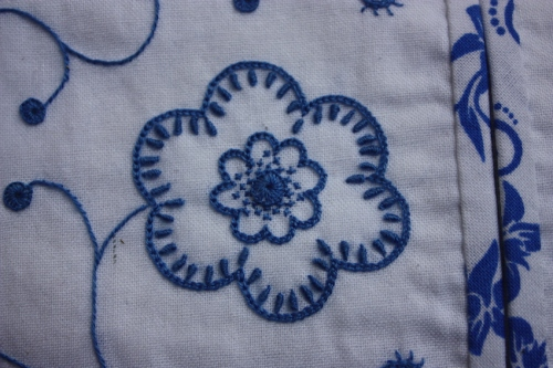 This flower is stitched with chain stitch, bullion knots, cross stitch, and buttonhole pinwheel.