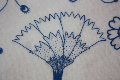 The central flower, a carnation, embroidered with...