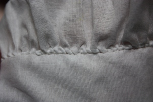 "The collar frill, gathered with a ""whipped-stitch-gather"" stitch and attached to the collar with a whipstitch."
