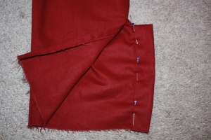 The placket has been folded to the inside and pinned down, ready to be sewn.