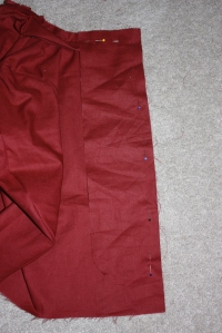 The facing is sewn, right sides together, to the front of the jacket.