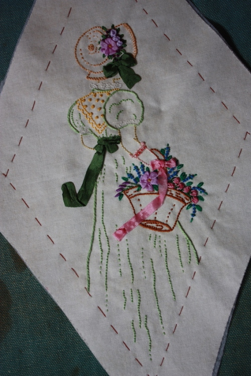 An embroidery of a Regency lady with a basket of flowers.