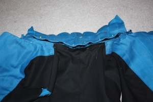 The collar is attached to the jacket, with the raw edges turned under and hand-sewn.