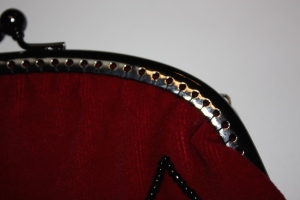 The bag sewn to the metal clasp, showing the vertical (rather than horizontal stitches).