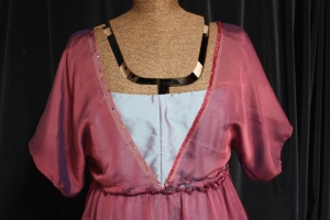 The sequins are handsewn around the neck edge of the sleeves.