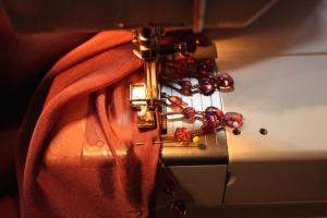 The beaded fringe is sewn on by machine, turning up the zigzagged edge.