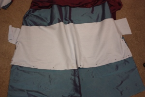 The front hem facing is pinned and cut to shape to match the skirt.