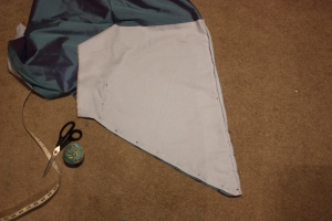 The back hem is cut to form a pointed train and the hem facing pinned ready to sew.