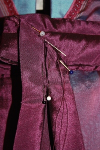 The smaller sash is attached on an angle on the right side of the waistband. It hangs down over the larger sash.
