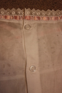 The button placket. The ribbon threaded through the entreduex is attached at the centre back so as not to come undone.
