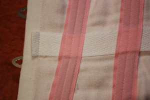 The inside of the corset, showing the boning channels sewn over the top of the waist tape.