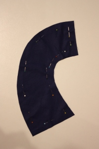The collar pattern piece, with the bottom edge being the centre front, and the top edge meeting at the centre back.